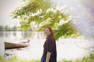 Portrait smiling woman at sunny lakeside Stock Photos