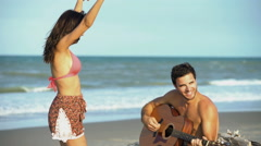 Smiling Caucasian American man playing the guitar and Hispanic woman dancing  Stock Footage
