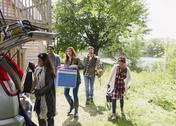Friends loading cooler and belongings into car outside sunny cabin Stock Photos