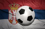 Black and white football ball on the national flag of serbia Stock Photos