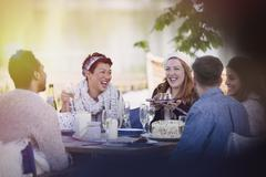Friends laughing eating cake and drinking champagne at patio table Stock Photos