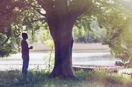 Man drinking coffee below tree at idyllic lakeside Stock Photos