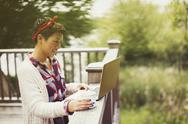 Woman drinking coffee and using laptop at balcony railing Stock Photos