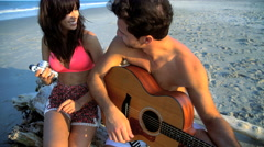Young smiling multi ethnic couple in swimwear having fun and playing the guitar Stock Footage
