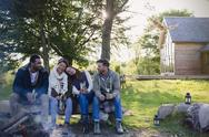 Friends drinking beer relaxing at campfire outside cabin Stock Photos