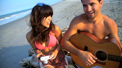 Young smiling multi ethnic couple in swimwear chilling and playing the guitar  Stock Footage