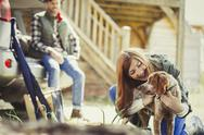 Woman petting dog outside cabin Stock Photos