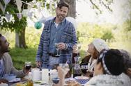 Man toasting friends at garden party table Stock Photos