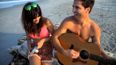 Young happy Hispanic woman taking photo of Caucasian man playing the guitar  Stock Footage
