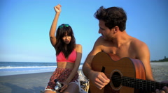 Young smiling multi ethnic couple in swimsuits chilling and playing the guitar Stock Footage