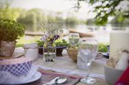 Place settings and simple bouquet on garden party table at lakeside Stock Photos