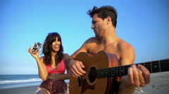 Young attractive Hispanic woman taking photo of Caucasian man playing the guitar Stock Footage