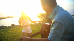 Hispanic woman taking photo of Caucasian man playing the guitar on their beach Stock Footage