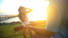 Hispanic woman making video diary of Caucasian man playing the guitar  Stock Footage