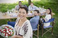 Portrait smiling woman serving Caprese salad to friends at garden party table Stock Photos