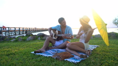 Multi ethnic man and woman relaxing with picnic and playing the guitar on beach Stock Footage