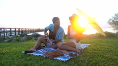 Smiling multi ethnic male and female enjoying picnic playing the guitar  Stock Footage