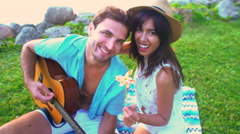 Portrait of young multi ethnic couple making video diary enjoying picnic playing Stock Footage