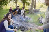 Friends hanging out playing guitar at campfire Stock Photos