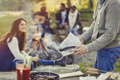 Man preparing hot dogs and fish at campfire Stock Photos