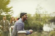 Smiling man drinking coffee at lakeside balcony Stock Photos