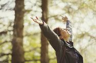 Exuberant woman hiking in sunny woods with head back and arms raised Stock Photos