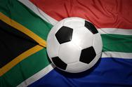 Black and white football ball on the national flag of south africa Stock Photos