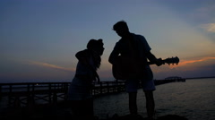 Silhouette of male and female enjoying dancing party with guitar on their beach Stock Footage