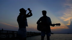 Silhouette of young man and woman dancing and playing the guitar on the beach  Stock Footage