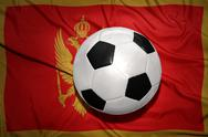 Black and white football ball on the national flag of montenegro Stock Photos