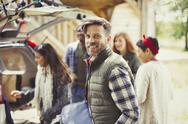 Portrait smiling man with friends unloading car Stock Photos
