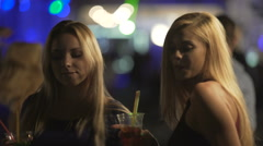 Beautiful women dancing with cocktails in hands, bisexual girls flirting in club Stock Footage