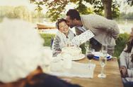 Boyfriend kissing girlfriend with birthday gift at lakeside patio table Stock Photos