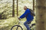 Smiling man riding mountain biking in woods Stock Photos