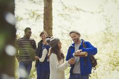 Smiling friends hiking pouring coffee from insulated drink container in woods Stock Photos