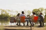 Friends toasting coffee mugs at sunny lakeside dock Stock Photos