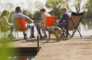 Friends and dog at sunny lakeside dock Stock Photos