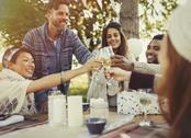 Friends toasting champagne glasses at birthday party patio table Stock Photos