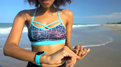 Beautiful fit African American female resting after health workout and checking Stock Footage