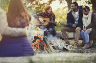 Friends playing guitar and drinking beer at campfire Stock Photos