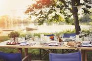 Garden party lunch on table at idyllic lakeside Stock Photos