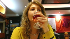 Beautiful young woman sips wine in a restaurant. Stock Footage