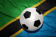 Black and white football ball on the national flag of tanzania Stock Photos