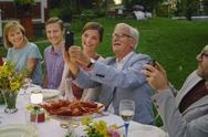 Senior man taking selfie with family at summer garden party dinner Stock Photos