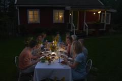 Family enjoying candlelight dinner at patio table outside house at night Stock Photos