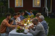 Family enjoying candlelight garden dinner party Stock Photos