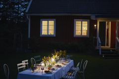 Candlelight garden party dinner outside illuminated house at night Stock Photos