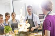 Students watching teacher flambe in cooking class kitchen Stock Photos
