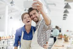 Enthusiastic couple taking selfie with camera phone in cooking class kitchen Stock Photos