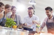 Students watching teacher in cooking class kitchen Stock Photos